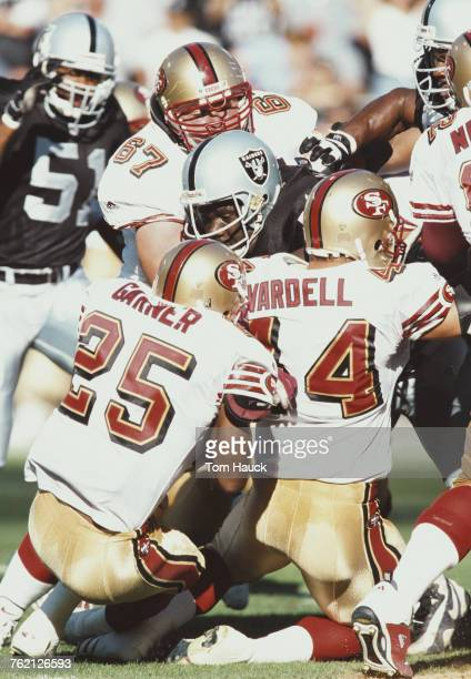 Russell Maryland Defensive Tackle for the Oakland Raiders tackles Charlie Garner and Tommy Vardell Running Backs for the San Francisco 49ers during...