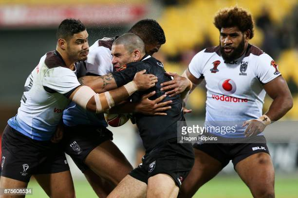 Russell Packer of the Kiwis is tackled by Brayden Wiliame and Jacob Saifiti of Fiji during the 2017 Rugby League World Cup Quarter Final match...