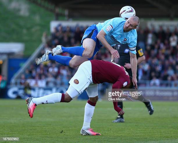 Russell Penn of Cheltenham Town rises above Ishmel Demontagnac of Northampton Town during the npower League Two Play Off Semi Final First Leg match...