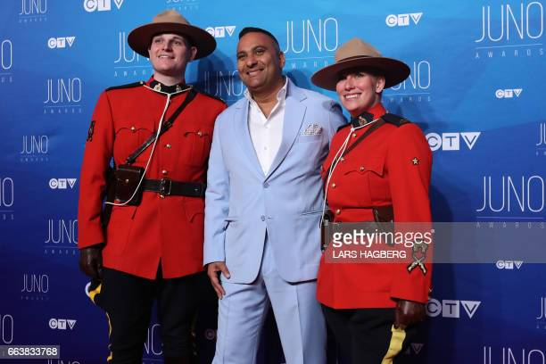 Russell Peters co host for the JUNO poses with two Mounties as he arrives on the red carpet before the JUNO awards at the Canadian Tire Centre in...