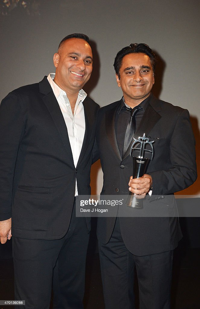 REQUIRED Russell Peters presents Sanjeev Bhaskar with the award for Outstanding Achievement in Television during The Asian Awards 2015 at The...