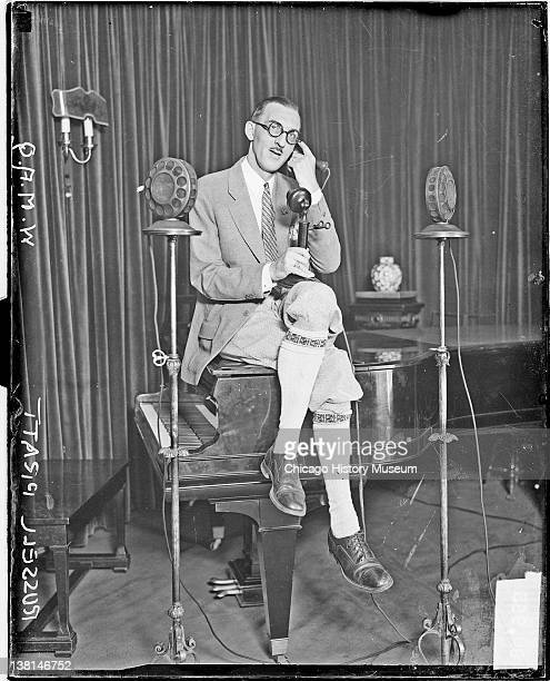 Russell Pratt of the Chicago Daily News radio station WMAQ sitting on top of a piano and talking on a telephone Chicago Illinois 1926 From the...