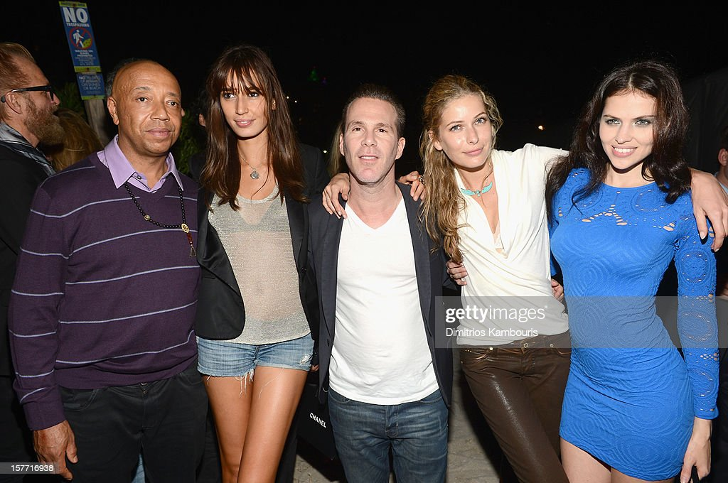 Russell Simmons (L) and Hana Nitsche and guests attend a Beachside Barbecue presented by CHANEL hosted by Art.sy Founder Carter Cleveland, Larry Gagosian, Wendi Murdoch, Peter Thiel and Dasha Zhukova at Soho Beach House on December 5, 2012 in Miami Beach, Florida.