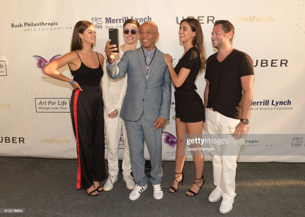 Russell Simmons poses for a selfie with guests during 'Midnight At The Oasis' Annual Art For Life Benefit hosted by Russell Simmons' Rush Philanthropic Arts Foundation at Fairview Farms on July 15, 2017 in Water Mill, New York.