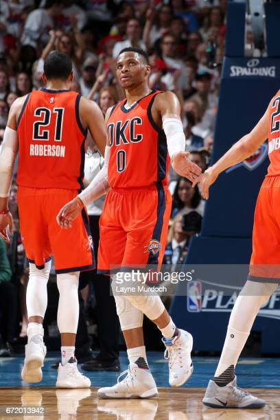 Russell Westbrook and Doug McDermott of the Oklahoma City Thunder high five each other during the game against the Houston Rockets in Game Four...