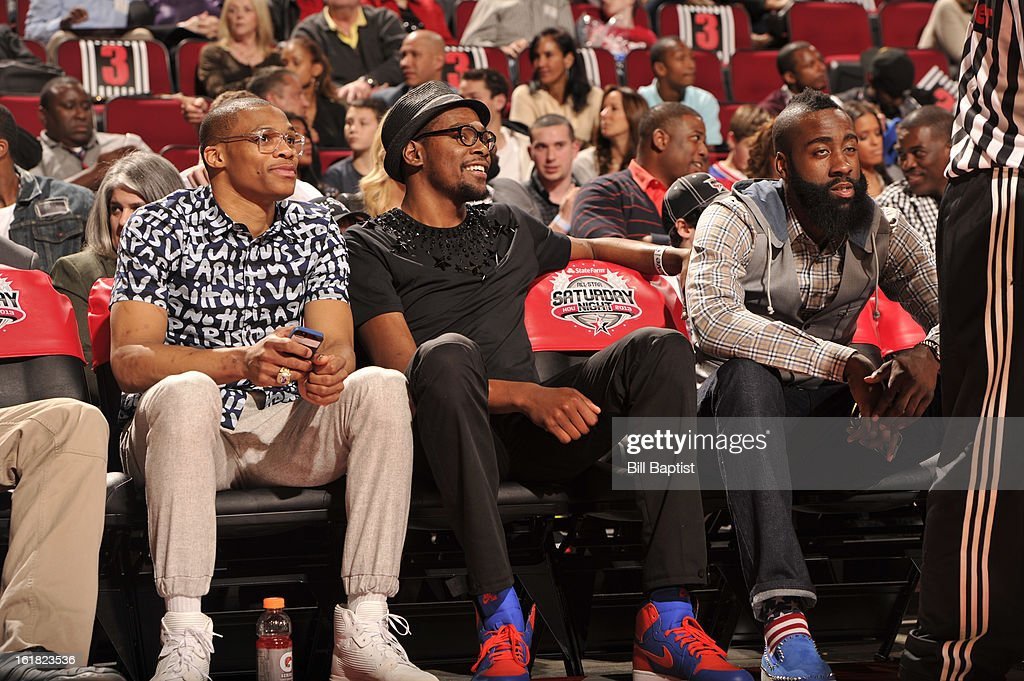 Russell Westbrook #0 and Kevin Durant #35 of the Oklahoma City Thunder and James Harden #13 of the Houston Rockets watch the 2013 Foot Locker Three-Point Contest on State Farm All-Star Saturday Night as part of 2013 NBA All-Star Weekend on February 16, 2013 at Toyota Center in Houston, Texas.