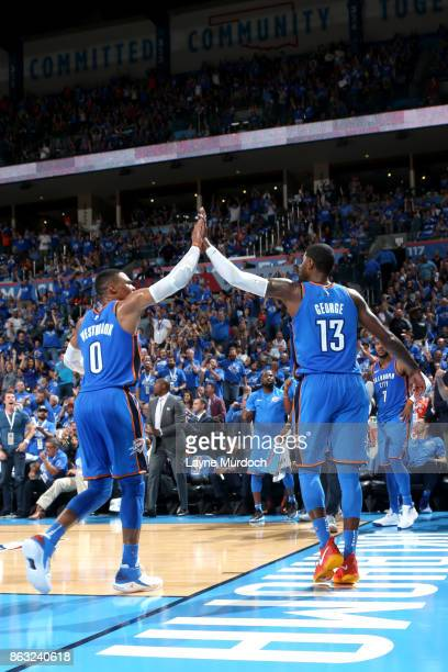 Russell Westbrook and Paul George of the Oklahoma City Thunder high five during the game against the New York Knicks on October 19 2017 at Chesapeake...