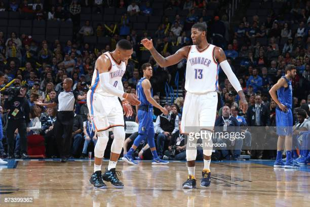 Russell Westbrook and Paul George of the Oklahoma City Thunder high five during the game against the Dallas Mavericks on November 12 2017 at...