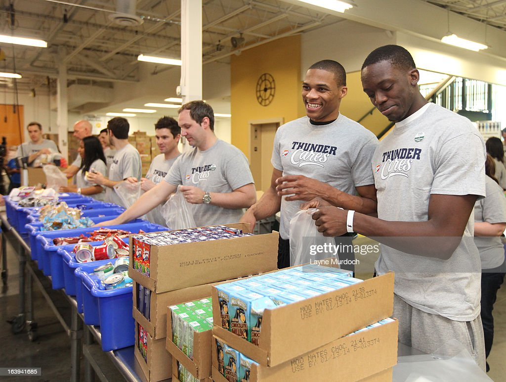 Russell Westbrook #0 and Reggie Jackson #15 of the Oklahoma City Thunder join Kids Cafe volunteers to assist with bagging and boxing food items for local families and schools on March 13, 2013 at the Regional Food Bank of Oklahoma in Oklahoma City, Oklahoma.
