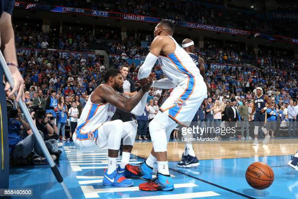 Russell Westbrook helps up Paul George of the Oklahoma City Thunder during the game against the New Orleans Pelicans during a preseason game on...