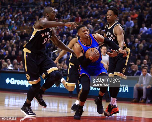 Russell Westbrook of the Oklahoma City Thunder dribbles the ball as Serge Ibaka and DeMar Derozan of the Toronto Raptors defend during the first half...