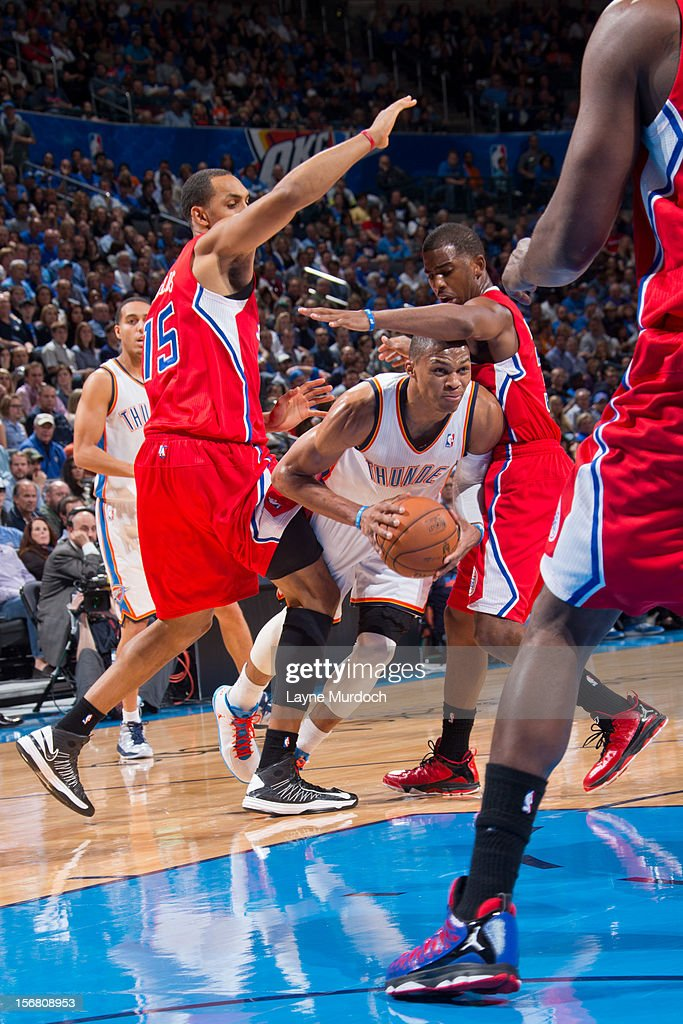 Russell Westbrook #0 of the Oklahoma City Thunder drives against Chris Paul #3 and Ryan Hollins #15 of the Los Angeles Clippers on November 21, 2012 at the Chesapeake Energy Arena in Oklahoma City, Oklahoma.