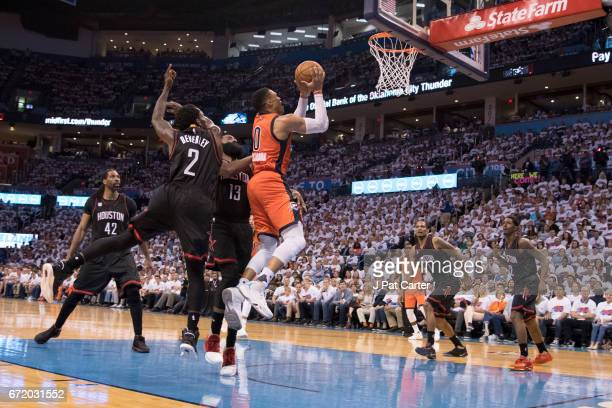 Russell Westbrook of the Oklahoma City Thunder drives between the Houston Rockets team for two points during the second half of Game Four in the 2017...