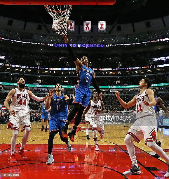 Russell Westbrook of the Oklahoma City Thunder drives the lane between Nikola Mirotic and Doug McDermott of the Chicago Bulls at the United Center on...