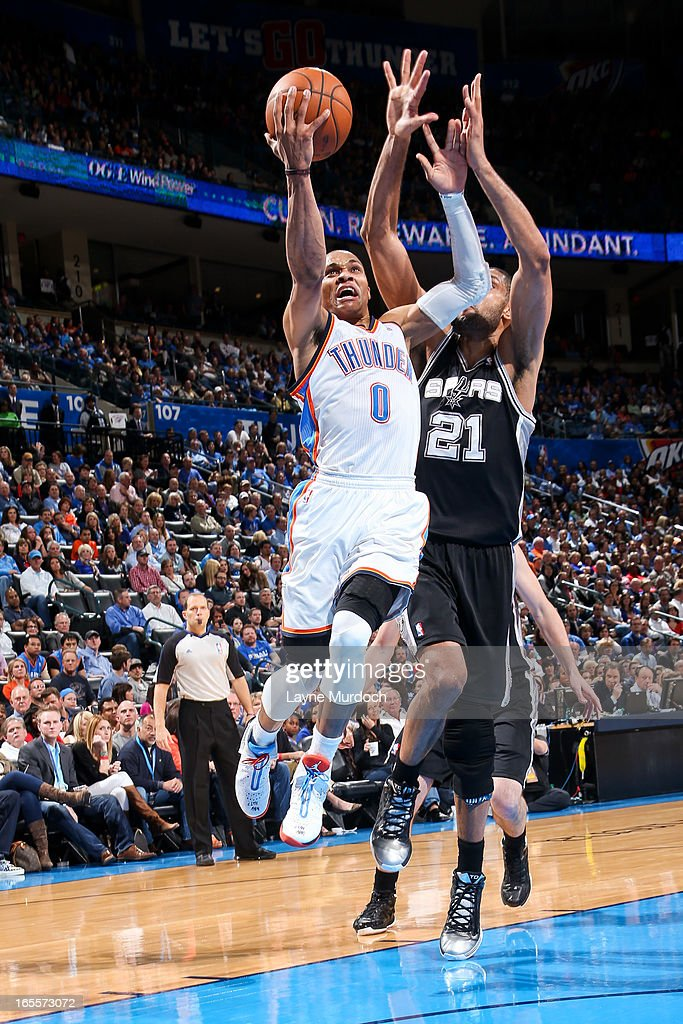 Russell Westbrook #0 of the Oklahoma City Thunder drives to the basket against Tim Duncan #21 of the San Antonio Spurs on April 4, 2013 at the Chesapeake Energy Arena in Oklahoma City, Oklahoma.