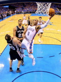 Russell Westbrook of the Oklahoma City Thunder drives to the basket against Manu Ginobili of the San Antonio Spurs in the first half during Game...