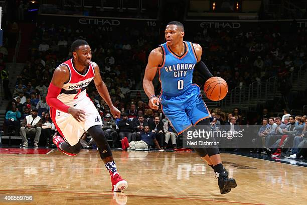 Russell Westbrook of the Oklahoma City Thunder drives to the basket against the John Wall of the Washington Wizards during the game on November 10...