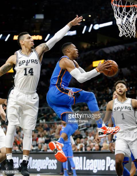 Russell Westbrook of the Oklahoma City Thunder drives under Danny Green of the San Antonio Spurs at ATT Center on November 17 2017 in San Antonio...