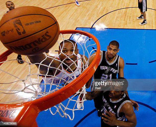Russell Westbrook of the Oklahoma City Thunder dunks the ball against Tim Duncan and Kawhi Leonard of the San Antonio Spurs in Game Six of the...