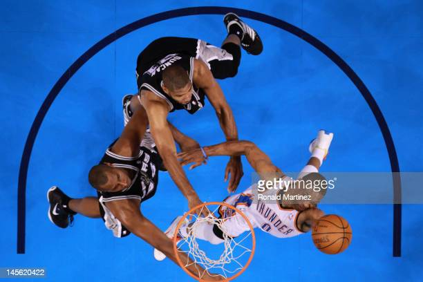 Russell Westbrook of the Oklahoma City Thunder goes up for a layup against Boris Diaw and Tim Duncan of the San Antonio Spurs in the first half in...
