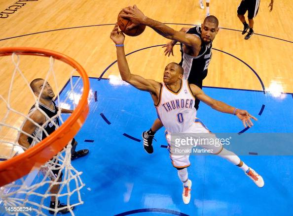 Russell Westbrook of the Oklahoma City Thunder goes up for the shot as Tim Duncan of the San Antonio Spurs attempts to block it from behind in the...