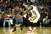 Russell Westbrook of the Oklahoma City Thunder is defended by Jrue Holiday of the New Orleans Pelicans during a game at the Smoothie King Center on...