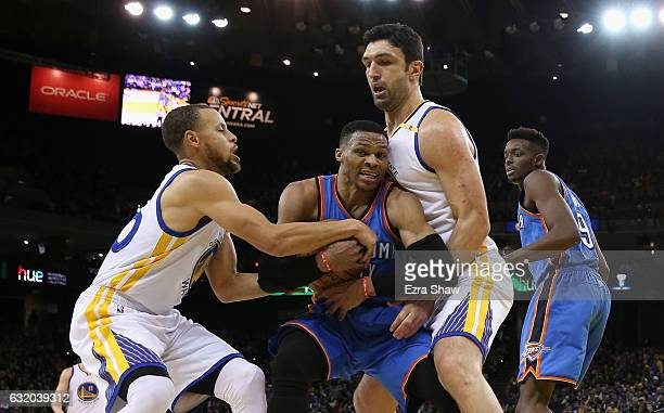Russell Westbrook of the Oklahoma City Thunder is guarded by Stephen Curry and Zaza Pachulia of the Golden State Warriors at ORACLE Arena on January...