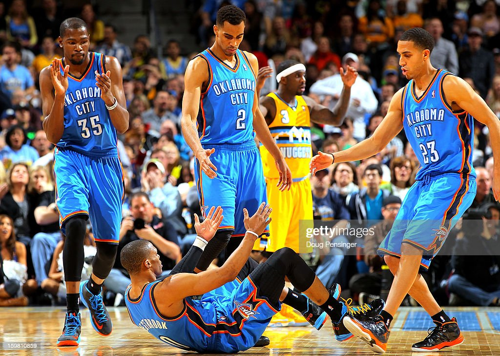 Russell Westbrook #0 of the Oklahoma City Thunder is helped to his feet by teammates Kevin Durant #35, Thabo Sefolosha #2 and Kevin Martin #23 of the Oklahoma City Thunder against the Denver Nuggets at the Pepsi Center on January 20, 2013 in Denver, Colorado. The Nuggets defeated the Thunder 121-118 in overtime.