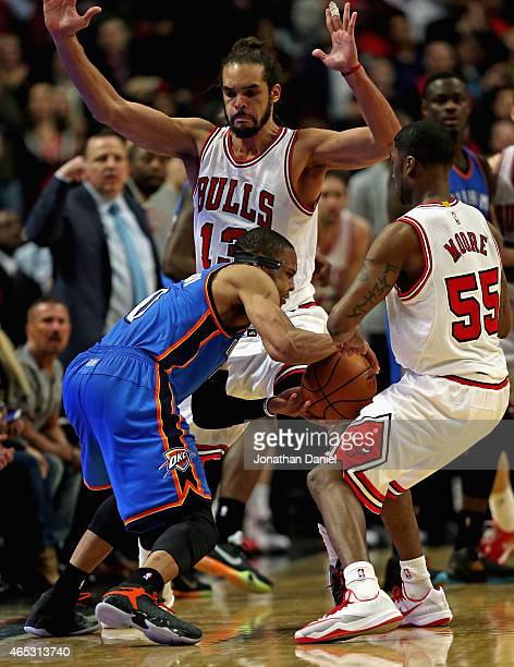 Russell Westbrook of the Oklahoma City Thunder is trapped by Joakim Noah and E'Twaun Moore of the Chicago Bulls and steps out of bounds in the...