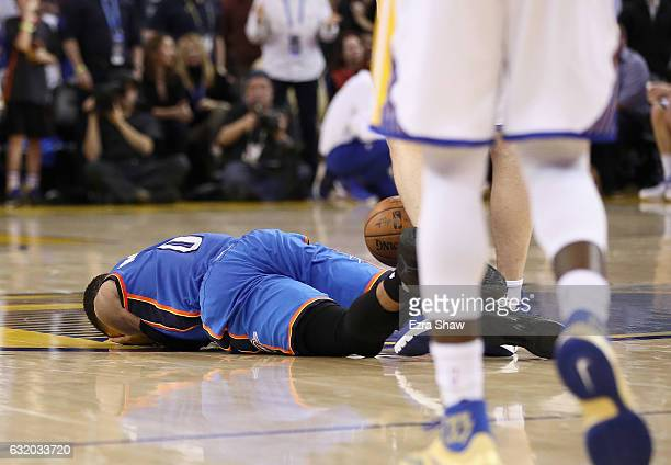 Russell Westbrook of the Oklahoma City Thunder lies on the court after being fouled by Zaza Pachulia of the Golden State Warriors at ORACLE Arena on...
