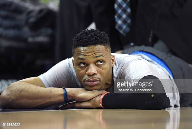 Russell Westbrook of the Oklahoma City Thunder looks on while being stretched as his team warms up prior to playing the Sacramento Kings in an NBA...