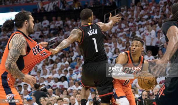 Russell Westbrook of the Oklahoma City Thunder looks to pass the ball as Trevor Ariza of the Houston Rockets hangs onto to Steven Adams of the...