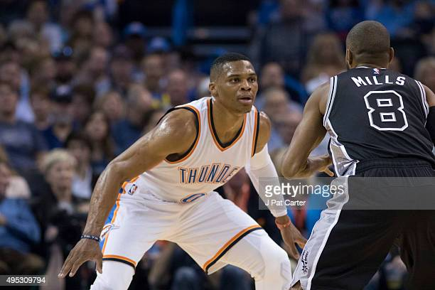Russell Westbrook of the Oklahoma City Thunder looks to stop Patty Mills of the San Antonio Spurs during the first quarter of a NBA game at the...