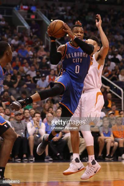 Russell Westbrook of the Oklahoma City Thunder makes a leaping pass ahead of Devin Booker of the Phoenix Suns during the first half of the NBA game...