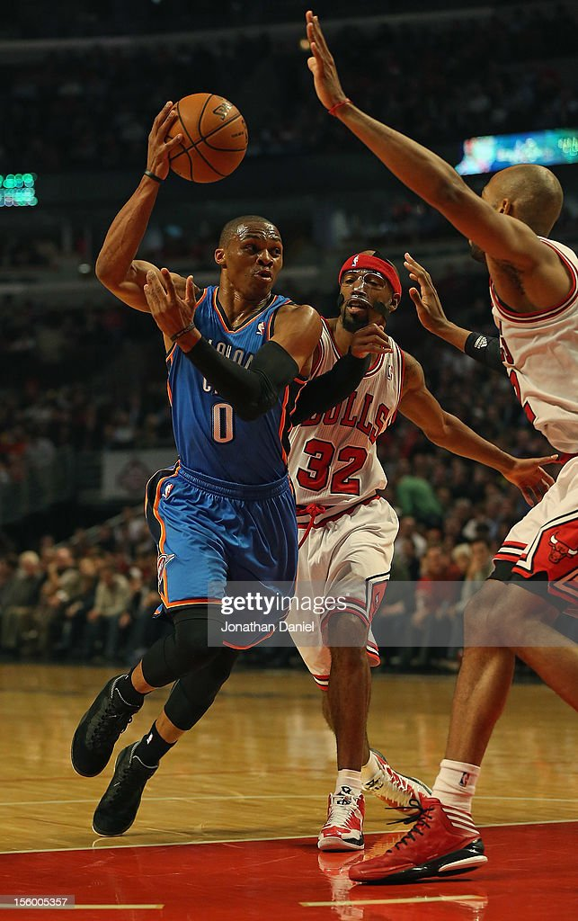 Russell Westbrook #0 of the Oklahoma City Thunder passes the ball between Richard Hamilton #32 and Taj Gibson #22 of the Chicago Bulls at the United Center on November 8, 2012 in Chicago, Illinois. The Thunder defeated the Bulls 97-91.