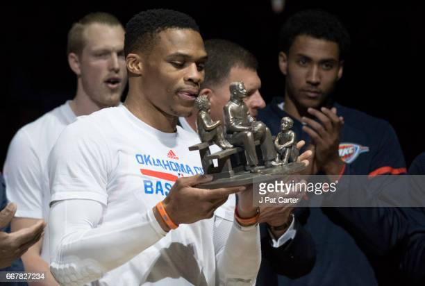 Russell Westbrook of the Oklahoma City Thunder receives the trophy for breaking former NBA great Oscar Robertson's tripledouble record during the...