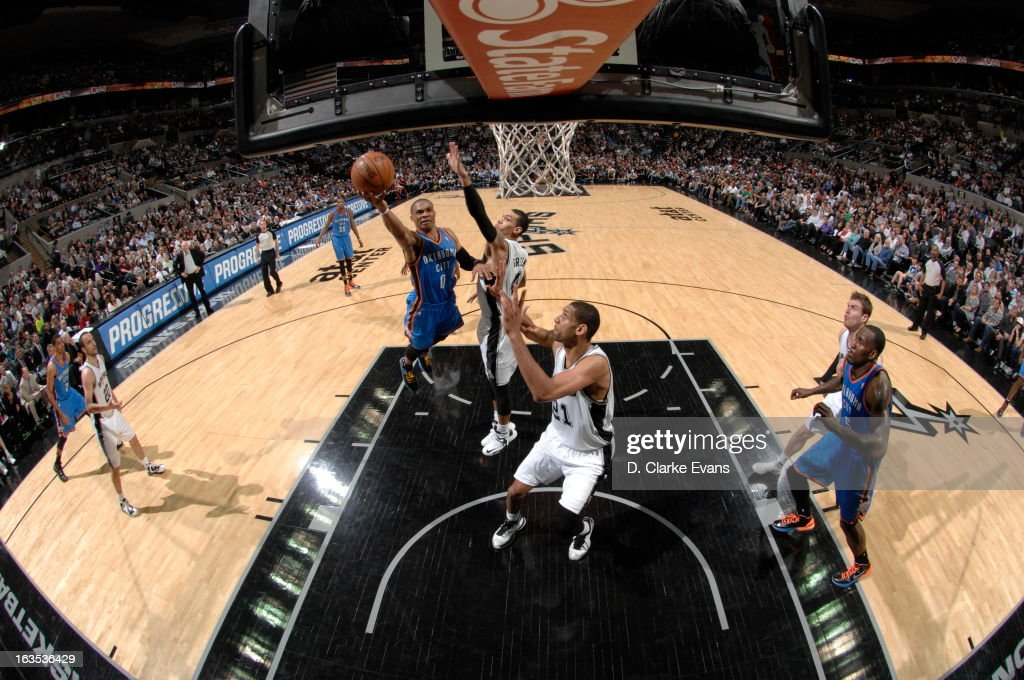 <a gi-track='captionPersonalityLinkClicked' href=/galleries/search?phrase=Russell+Westbrook&family=editorial&specificpeople=4044231 ng-click='$event.stopPropagation()'>Russell Westbrook</a> #0 of the Oklahoma City Thunder shoots a layup against Danny Green #4 and <a gi-track='captionPersonalityLinkClicked' href=/galleries/search?phrase=Tim+Duncan&family=editorial&specificpeople=201467 ng-click='$event.stopPropagation()'>Tim Duncan</a> #21 of the San Antonio Spurs on March 11, 2013 at the AT&T Center in San Antonio, Texas.