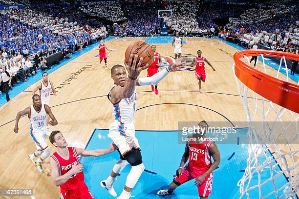 Russell Westbrook of the Oklahoma City Thunder shoots a layup ahead of Chandler Parsons and James Harden of the Houston Rockets in Game Two of the...