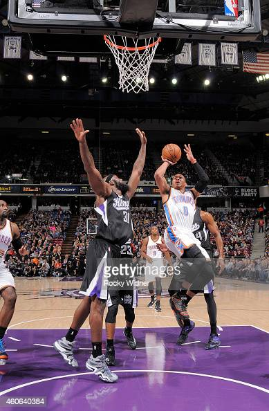 Russell Westbrook of the Oklahoma City Thunder shoots against Reggie Evans of the Sacramento Kings on December 16 2014 at Sleep Train Arena in...