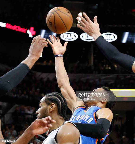 Russell Westbrook of the Oklahoma City Thunder shoots over Kawhi Leonard of the San Antonio Spurs at ATT Center on March 12 2016 in San Antonio Texas...