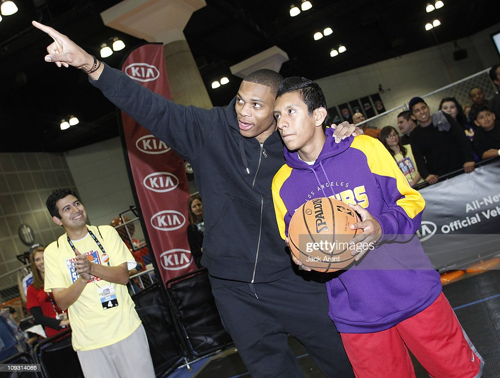 Russell Westbrook of the Oklahoma City Thunder shows a fan where to aim his shot on the Kia court during Jam Session presented by Adidas during All Star Weekend on February 20, 2011 in Los Angeles, California.
