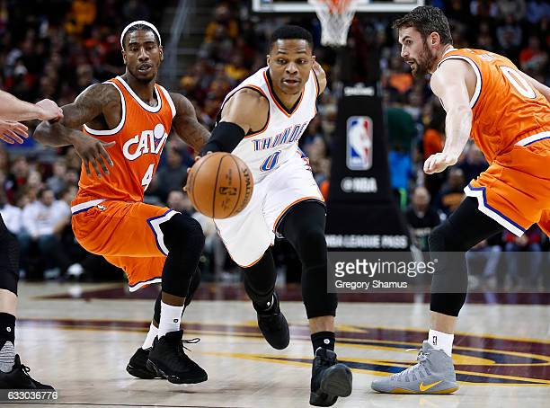 Russell Westbrook of the Oklahoma City Thunder splits the defense of Iman Shumpert and Kevin Love of the Cleveland Cavaliers during the first half at...