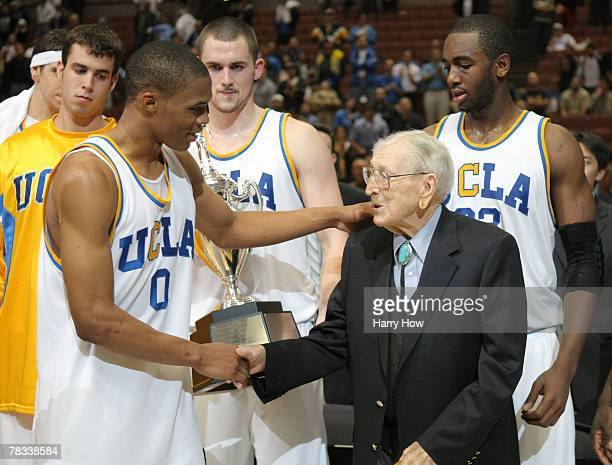 Russell Westbrook of the UCLA Bruins shakes hands with former college basketball coach John Wooden after a 7563 win over the Davidson Wildcats during...