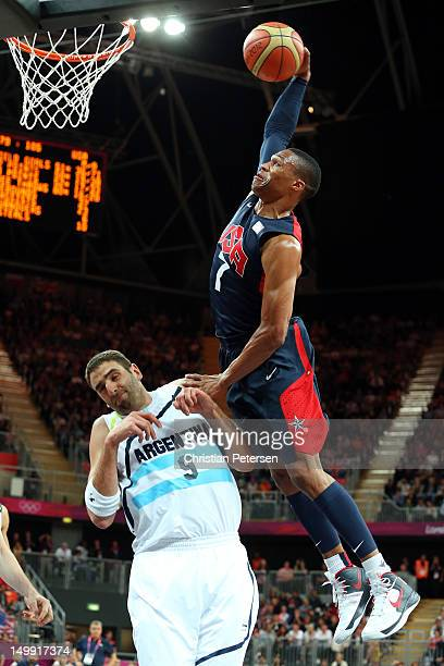 Russell Westbrook of United States dunks the ball over Juan Gutierrez of Argentina during the Men's Basketball Preliminary Round match on Day 10 of...