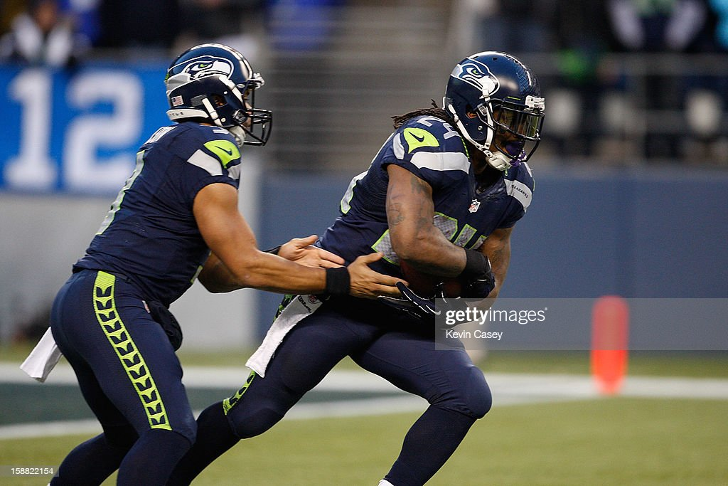 Russell Wilson #3 (L) hands off to running back Marshawn Lynch #24 of the Seattle Seahawks against the St. Louis Rams in the first half at CenturyLink Field on December 30, 2012 in Seattle, Washington.