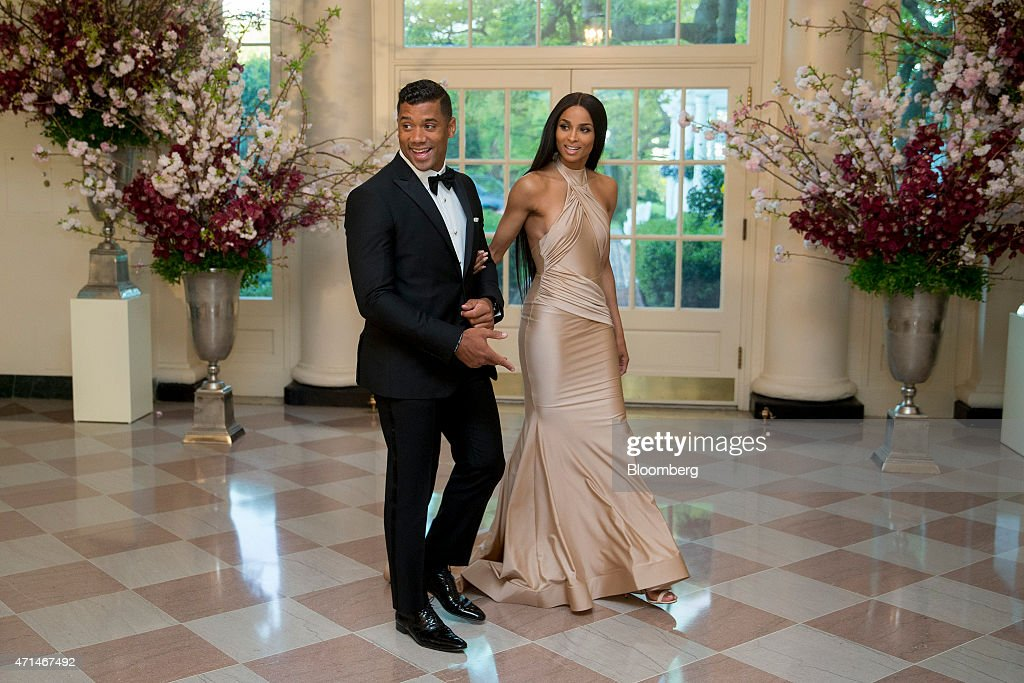 Russell Wilson, National Football League (NFL) quarterback for the Seattle Seahawks, left, and singer Ciara Harris speak to the media as they arrive at a state dinner hosted by U.S. President Barack Obama and U.S. First Lady Michelle Obama in honor of Japan's Prime Minister Shinzo Abe at the White House in Washington, D.C., U.S., on Tuesday, April 28, 2015. Prime Minister Shinzo Abe goes before the U.S. Congress on Wednesday to present Japan as a stalwart ally that's willing to play a bigger military role in Asia, a message likely to be embraced in Washington and greeted with suspicion in Seoul and Beijing. Photographer: Andrew Harrer/Bloomberg via Getty Images