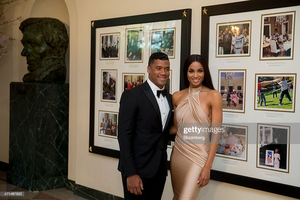 Russell Wilson, National Football League (NFL) quarterback for the Seattle Seahawks, left, and singer Ciara Harris arrive at a state dinner hosted by U.S. President Barack Obama and U.S. First Lady Michelle Obama in honor of Japan's Prime Minister Shinzo Abe at the White House in Washington, D.C., U.S., on Tuesday, April 28, 2015. Prime Minister Shinzo Abe goes before the U.S. Congress on Wednesday to present Japan as a stalwart ally that's willing to play a bigger military role in Asia, a message likely to be embraced in Washington and greeted with suspicion in Seoul and Beijing. Photographer: Andrew Harrer/Bloomberg via Getty Images
