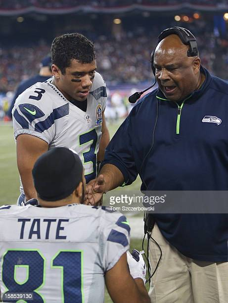 Russell Wilson of the Seattle Seahawks and wide receivers coach Kippy Brown talk to Golden Tate during an NFL game against the Buffalo Bills at...