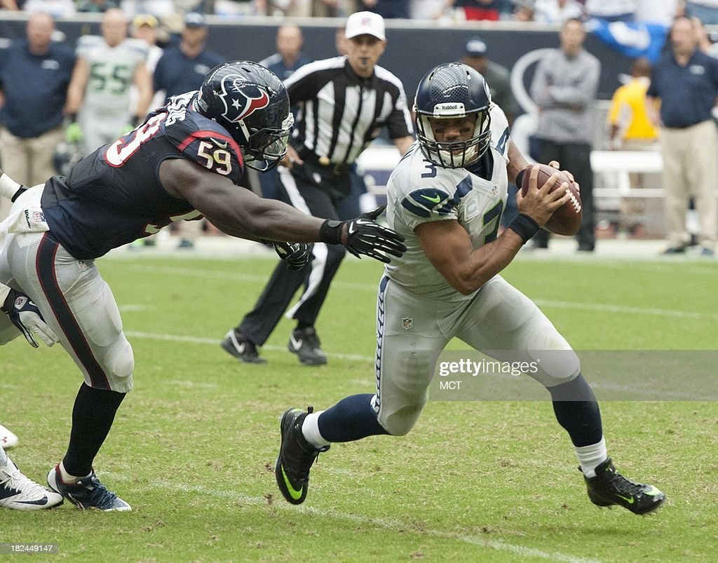 Russell Wilson (3) of the Seattle Seahawks eludes the tackle of Whitney Mercilus (59) of the Houston Texans in the second half of a 23-20 Seattle overtime victory on Sunday, September 29, 2013, in Houston, Texas.