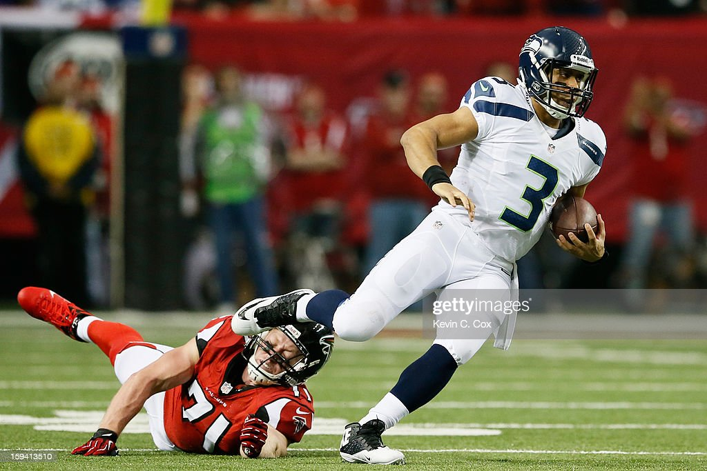 Russell Wilson #3 of the Seattle Seahawks escapes the tackle of Kroy Biermann #71 of the Atlanta Falcons in the second quarter of the NFC Divisional Playoff Game at Georgia Dome on January 13, 2013 in Atlanta, Georgia.
